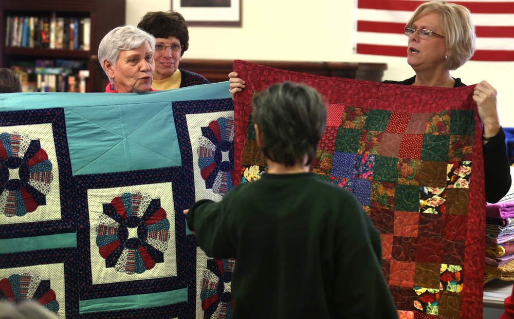 Decisions, decisions. A resident of the nursing home points to a quilt that would soon be his held by Home and Community Education member Virginia Duvall at left. Holding the other quilt at right is Mary Johnson. David Spencer/The State Journal-Register