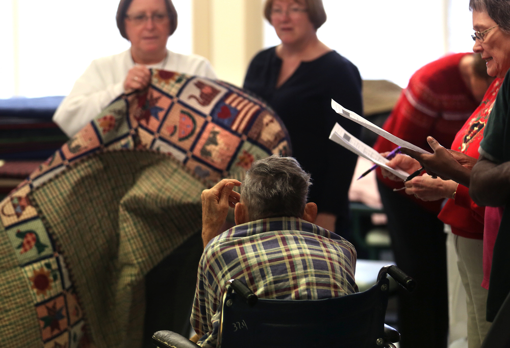 A nursing home resident in a wheelchair ponders his new quilt held by Home and Community Education member Vi Lanum at left. David Spencer/The State Journal-Register