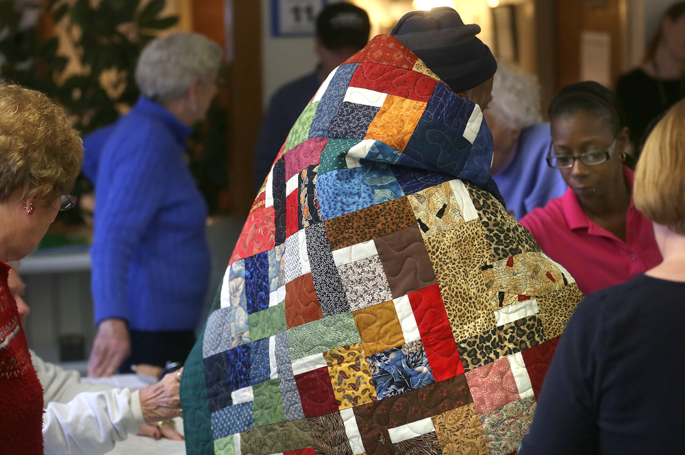 One of the residents didn't take long to use his new quilt as a body wrap, and is helped by an employee of the facility at right during the presentation ceremony. David Spencer/The State Journal-Register