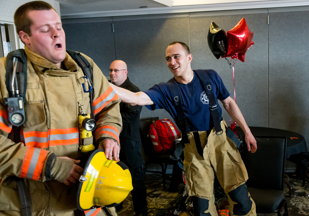 Springfield firefighter Justin Stewart, center, gives pat on the back to fellow firefighter Lance Miller, left, as he finishes the 32 flight climb during the American Lung Association in IllinoisÕ 2015 Fight for Air Climb at the Hilton, Sunday, Feb. 8, 2015, in Springfield, Ill. Justin L. Fowler/The State Journal-Register