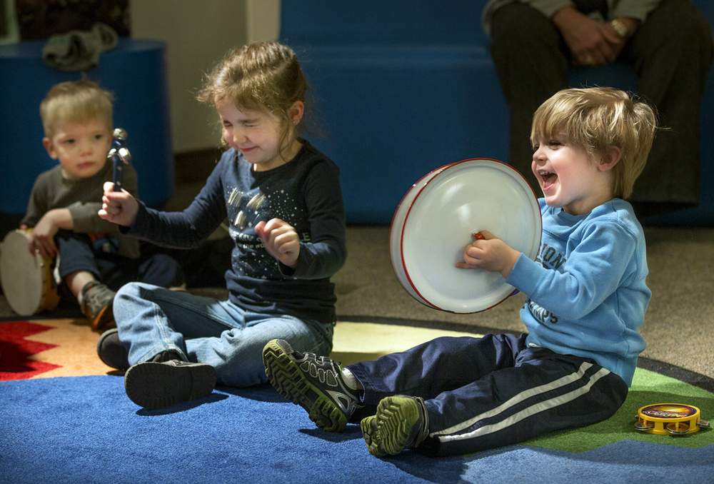"Claira Leonard, right, closes her eyes as she rattles her sleigh bells and Dominic VanDerWal crashes two pot lid cymbals together during a brief concert at the conclusion Story Time at the Museum: Catch the Beat at the Illinois State Museum Monday, Feb. 9, 2015. Musician Mark McKnight read ""Charlie Parker Played Be Bop"" by Christopher Raschka before distributing the percussion instruments for the children to play. Ted Schurter/The State Journal-Register"