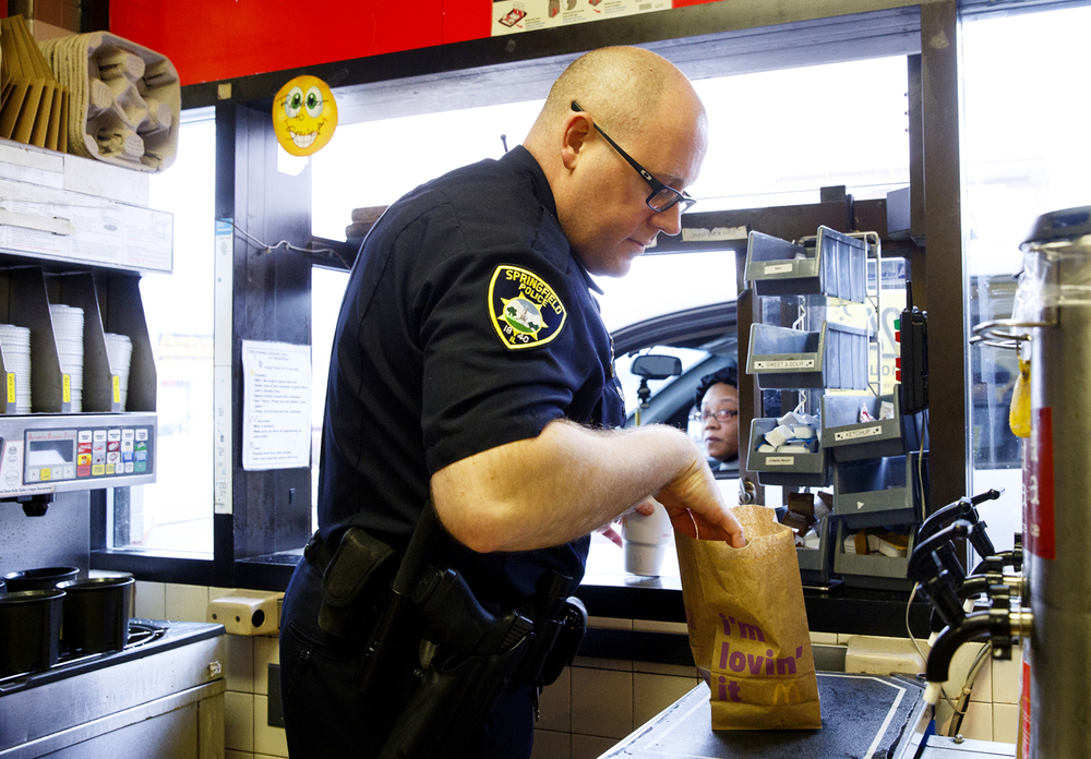 Springfield Police Officer Edward Higginson double checks an order before passing it through the drive-up window at McDonald's on South Grand Avenue East Wednesday, Feb. 11, 2015. Higginson and other Springfield officers participated in a Coffee with a Cop event where residents had a chance to visit informally one-on-one with officers. Some of the officers took turns greeting people and handing them their order at the window. Rich Saal/The State Journal-Register
