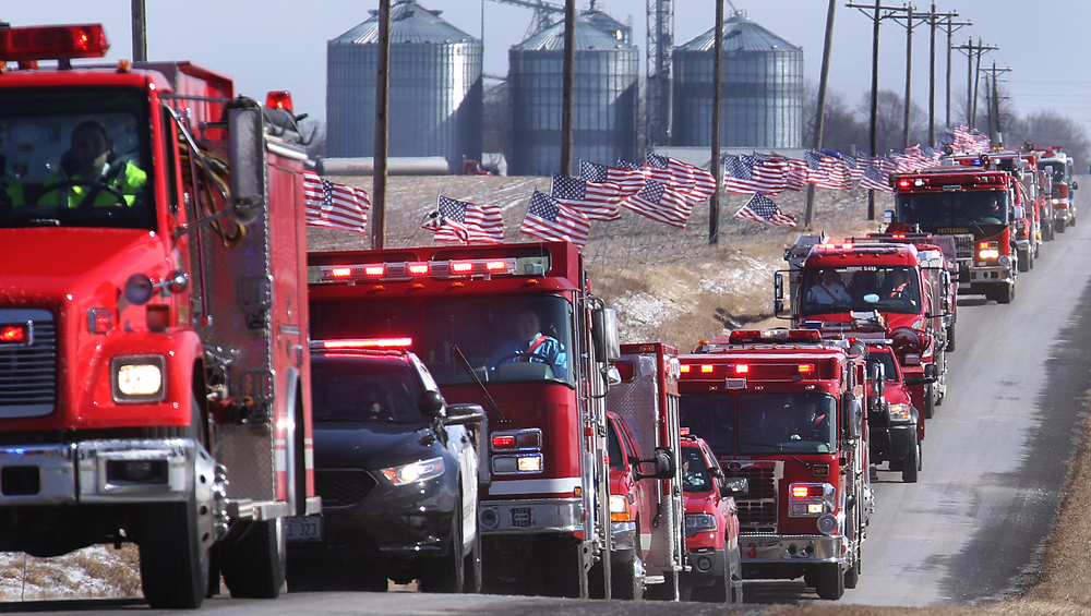 With thousands of American flags lining the funeral route from the high school to the cemetery, a column of over 60 firetrucks, with the final one transporting Lehr's casket, slowly make their way down Kane Rd. near the cemetery late Saturday morning. David Spencer/The State Journal-Register