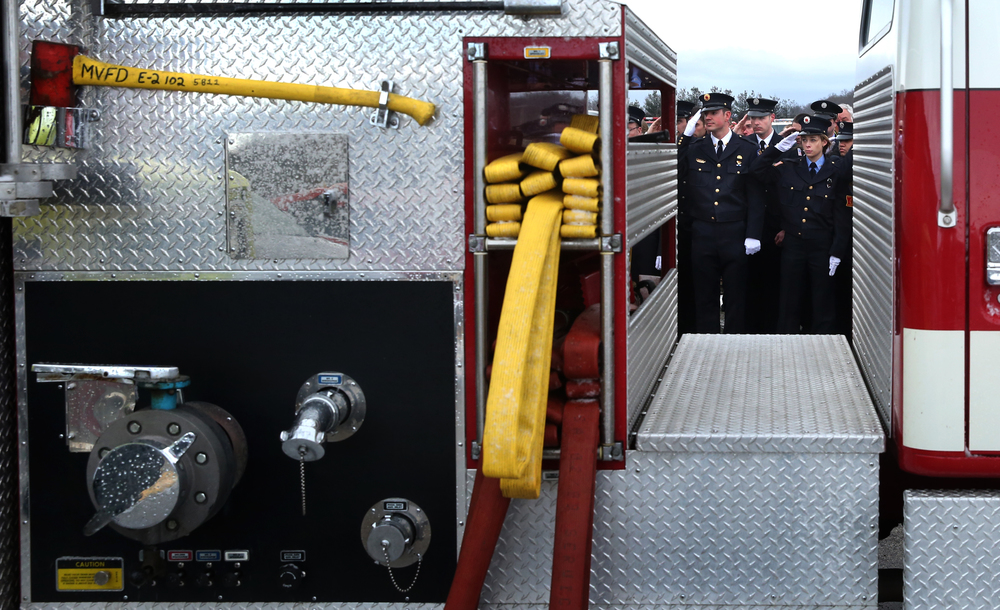 A column of firefighters saluting during the transfer of the Chief Lehr's casket from the school to the top of a Medora fire truck can be seen framed on the other side of Medora fire engine No. 2. David Spencer/The State Journal-Register