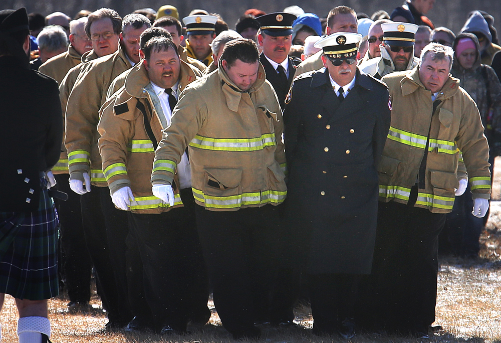 Medora volunteer firefighters act as pallbearers as they make the final walk to graveside with Chief Lehr's casket at Maple Lawn Cemetery late Saturday morning. David Spencer/The State Journal-Register