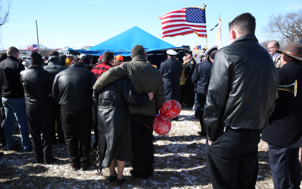 A couple holding several red balloons eventually released during graveside services for Chief Lehr hold each other on a bitter cold morning.David Spencer/The State Journal-Register