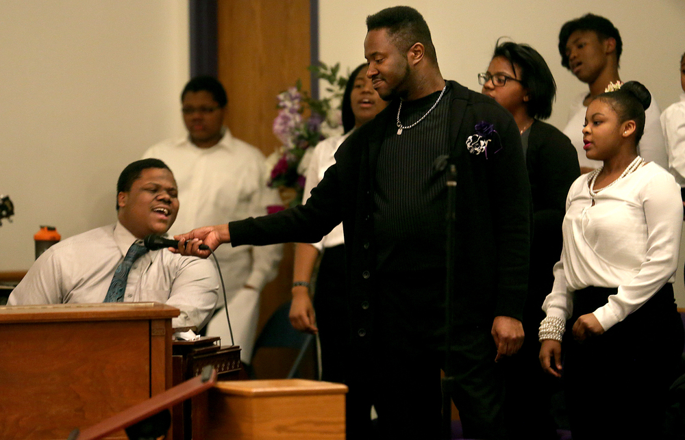 Using a microphone, Wood River youth choir director Kenneth Higgins Jr. further amplifies the sound coming from a joyful Clifton Jones, the organist at Springfield's Fresh Visions Community Church who was playing the keyboard. David Spencer/The State Journal-Register