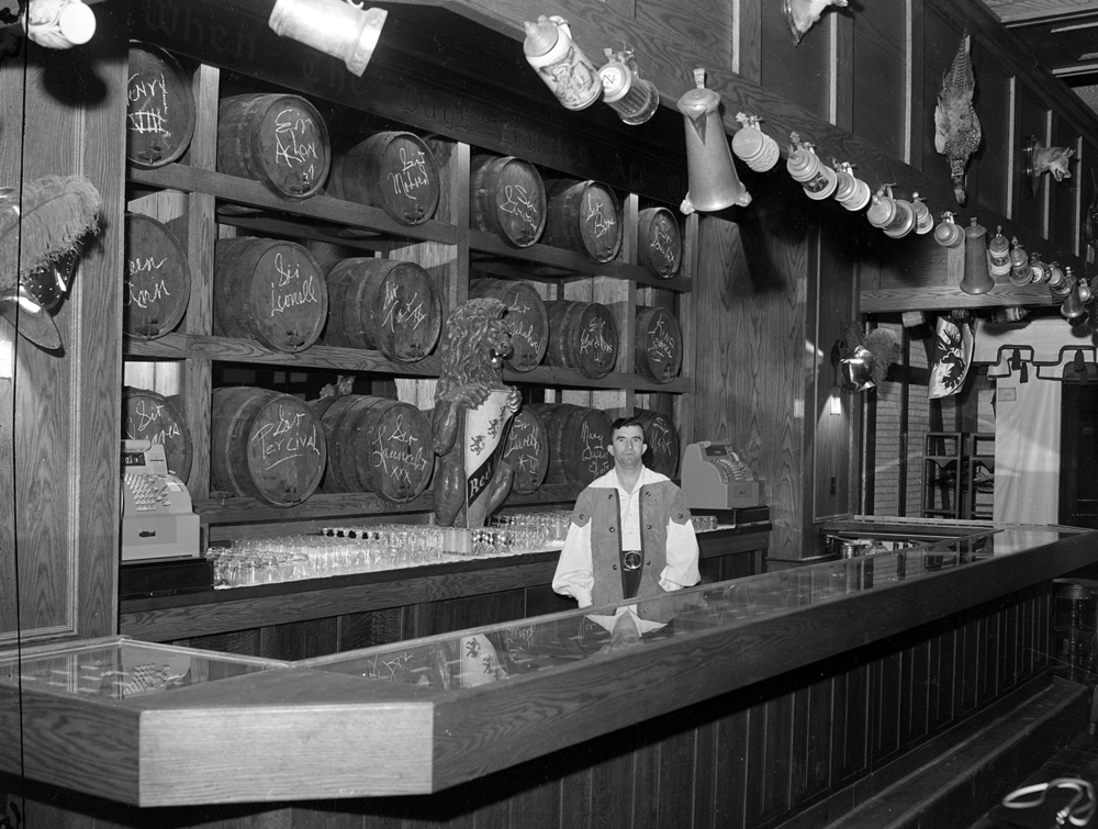 "The ""swashbuckling bartender,"" who was not identified, is dwarfed by the bar backdrop. A mirror 16-feet wide by 7-feet tall, it was covered with whiskey barrels cut in half, giving the effect of whole barrels sticking through the plate glass. On the end of each barrel was written the name of a Knight of the Round Table. File/The State Journal-Register"