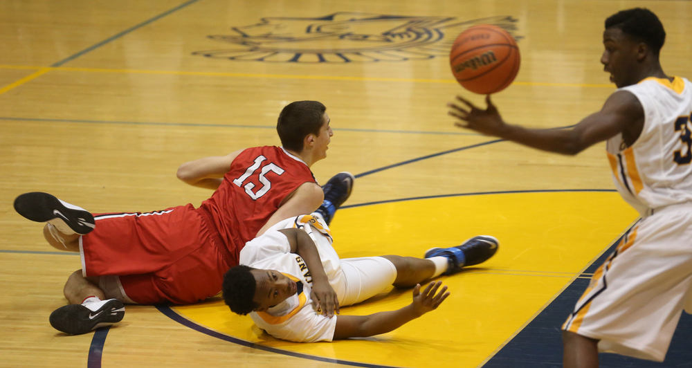 On the floor, Southeast's Mark Johnson collides with Glenwood's Joel Alexander while watching the ball tip to Johnson's teammate D'Angelo Hughes at right.  Southeast defeated Glenwood 47-44 in boys basketball action at Southeast's Scheffler Gymnasium in Springfield on Friday evening, Feb. 20, 2015. David Spencer/The State Journal-Register