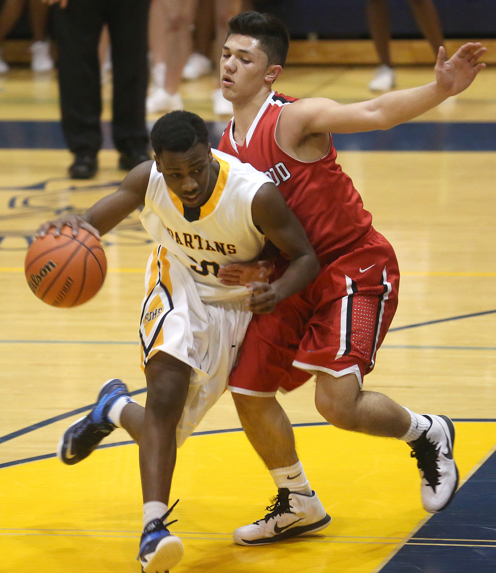Southeast's D'Angelo Hughes drives around Glenwood defender Drew Parriott. Southeast defeated Glenwood 47-44 in boys basketball action at Southeast's Scheffler Gymnasium in Springfield on Friday evening, Feb. 20, 2015. David Spencer/The State Journal-Register