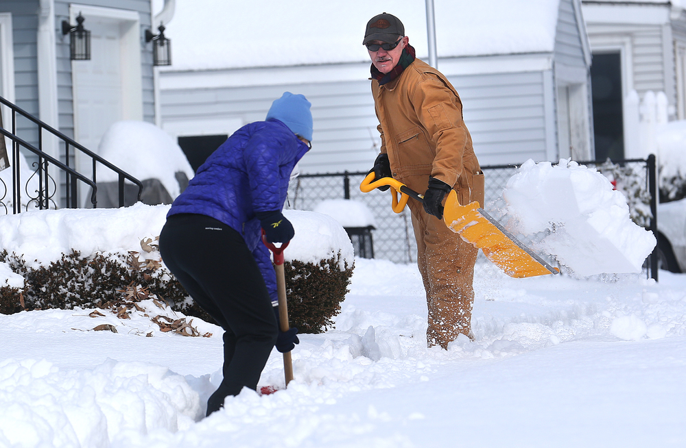 Near Edwards St. and Amos Ave., neighbors Ron Duff, right and Suzie Fessler work as a team clearing the sidewalks around their homes Saturday morning. On Saturday, the Springfield area began digging out of its most significant winter storm of the season after nearly a foot of snow fell. The National Weather Service's official snow total for the capital city was 11.8 inches, as of 6 a.m. A total of 8.9 inches of snow fell at Abraham Lincoln Capital Airport Friday night, breaking the previous record for Feb. 20 of 3.6 inches set in 1989, the weather service reported. David Spencer/The State Journal-Register