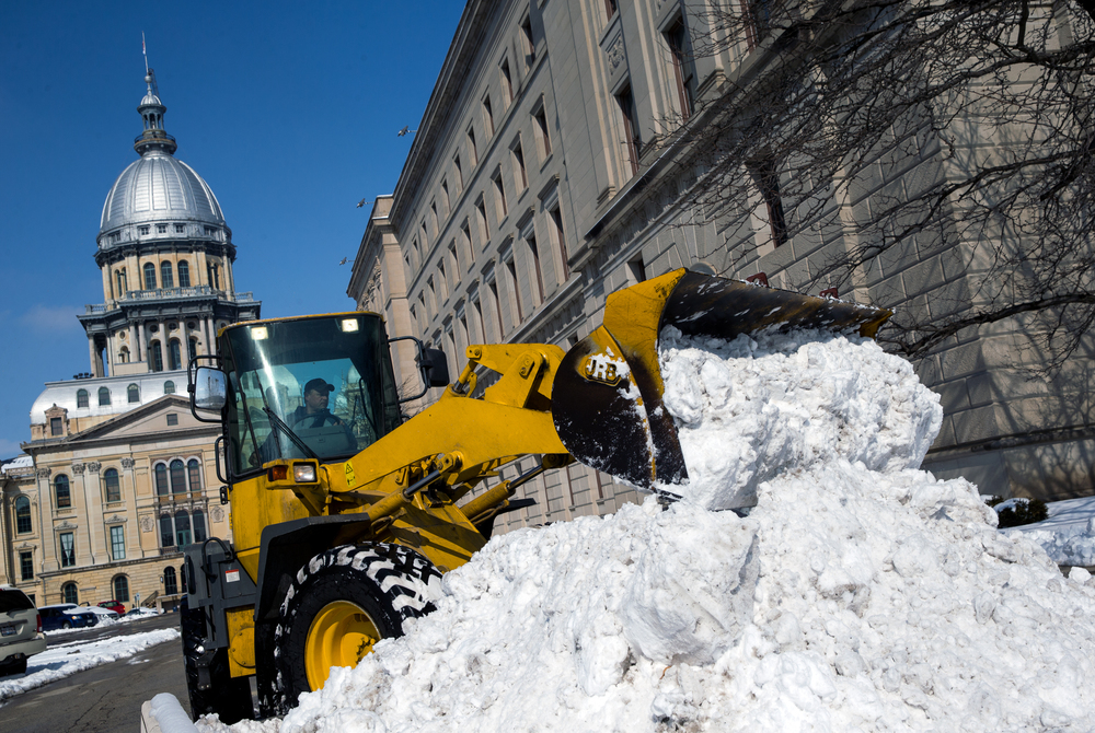 Crews work to clear the snow from the Illinois State Capitol complex after an overnight storm dumped nearly a foot of snow across the area, Saturday, Feb. 21, 2015, in Springfield, Ill. Justin L. Fowler/The State Journal-Register