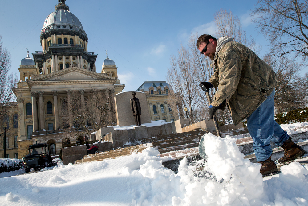Mark Leigh, of Virden, Ill., a yard maintenance work with the Illinois Secretary of State, clears snow from the steps of the Illinois State Capitol, Saturday, Feb. 21, 2015, in Springfield, Ill. Crews were out clearing the snow from the Capitol complex in hopes of removing it before colder temperatures hit the area. Justin L. Fowler/The State Journal-Register