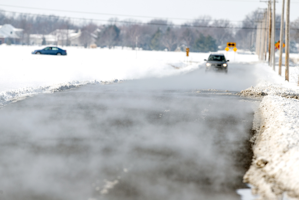 Steam rises up from Iles Avenue as the sun begins melting away nearly a foot of snow that fell across the area overnight, Saturday, Feb. 21, 2015, in Springfield, Ill. Justin L. Fowler/The State Journal-Register