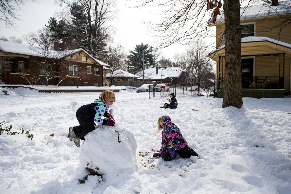 Apple DeWeese, 5, and her sister Ada DeWeese, 8, used the nearly foot of snow to start building a snowman while their father shoveled the sidewalks, Saturday, Feb. 21, 2015, in Springfield, Ill. Justin L. Fowler/The State Journal-Register