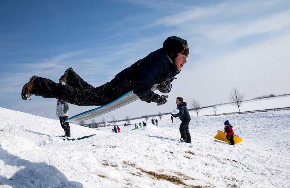 "Ayden Oldfield, 15, of Rochester, Ill., goes airborne off a ramp made of snow while hitting the slopes of Centennial Park after nearly a foot of snow fell across the area, Saturday, Feb. 21, 2015, in Springfield, Ill. ""It knocks the wind out of you as soon as you hit the ground,"" said Oldfield of the experience. Justin L. Fowler/The State Journal-Register"