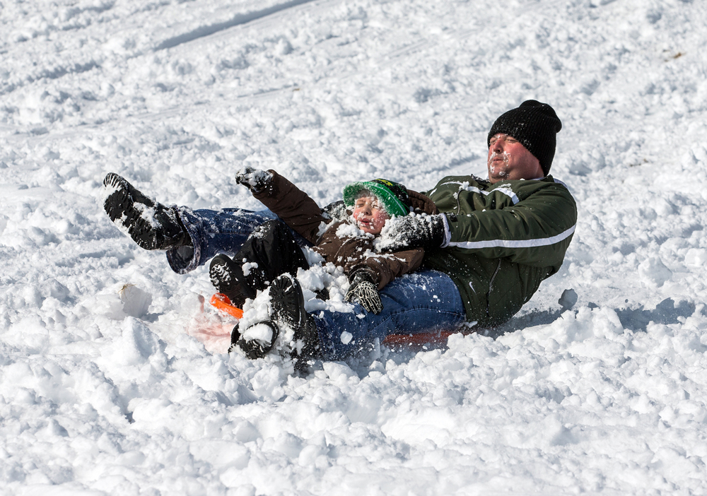 "Steve Blum and son Logan, 5, get face full of snow as they hit the bottom of the slopes while sledding at Centennial Park, Saturday, Feb. 21, 2015, in Springfield, Ill. ""It's the first real chance to come out and sled and might as well take advantage of it,"" said Blum of the snow storm that brought nearly a foot of snow across the area. Justin L. Fowler/The State Journal-Register"