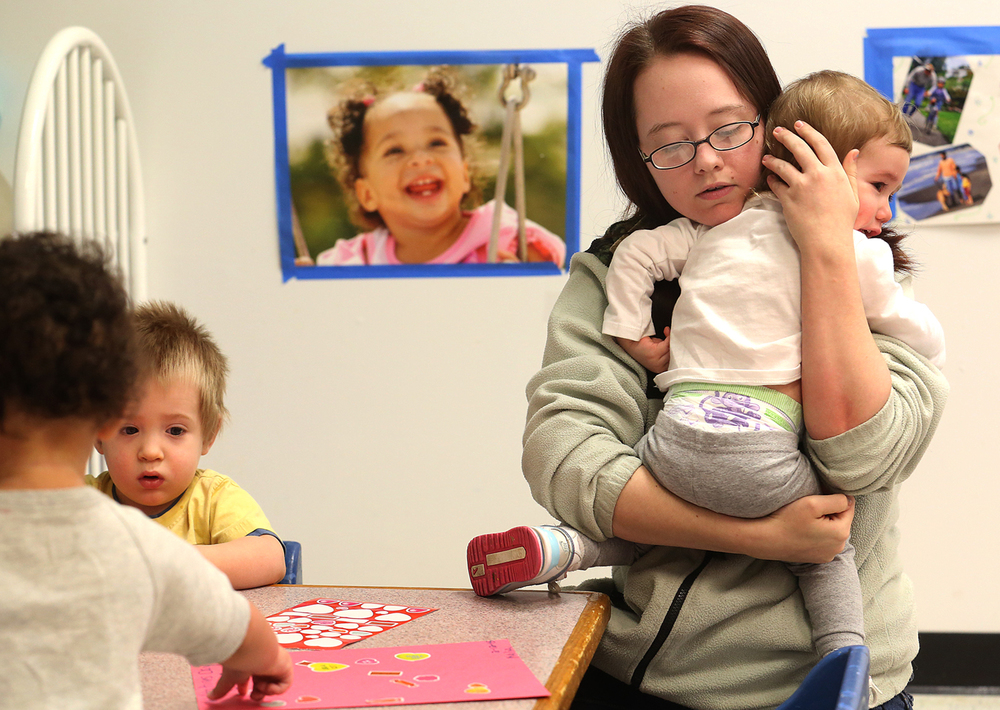 Development Center teacher Gina Hicks comforts Kalia Thompson, 20 months, during an activity session at the facility on Thursday, Feb. 12, 2015. At left are Brandon Bea, 19 months and Madilynn Lerch, 17 months. (back to camera) For the past 25 years, Penny Driver has owned Teddy Bear Christian Development Center in Riverton, a child daycare center for children six weeks to 12 years old, and is being financially impacted in a negative way by the state's funding crisis connected with the expiration of the temporary state income tax increase at the end of December. David Spencer/The State Journal-Register