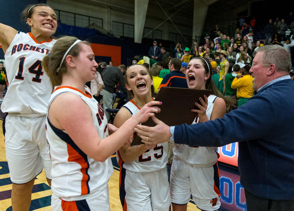 Rochester's Laryn Sapetti (32), Sydney Lett (25), Lucy Nuding (35) and Lyric Boone (14) celebrate with the trophy after the Rockets defeated Normal U-High 40-39 in the Girls Class 3A Rochester Sectional title game at the Rochester Athletic Complex, Thursday, Feb. 26, 2015, in Rochester, Ill. Justin L. Fowler/The State Journal-Register