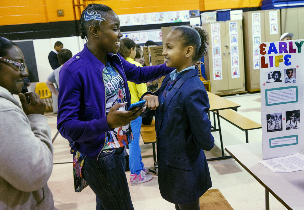 Michelle Hudson hugs her daughter Cheyenne Trotter  after watching her report on Emmet Till during the African American History Fair at Jane Addams Elementary School Monday, Feb. 23, 2015. Fifth grade students dressed as the African American historical figure they researched and performed a brief biography for fellow students and parents that attended the fair. Trotter's grandmother, Annette Hudson, is at left. Ted Schurter/The State Journal-Register