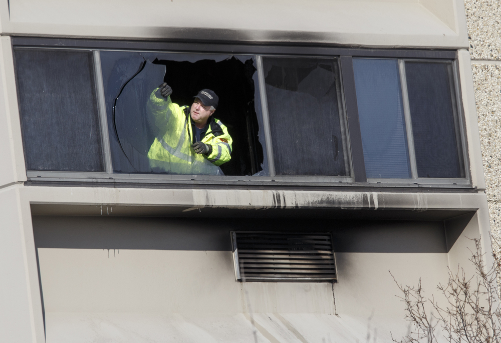 Investigators from the Springfield Fire Department remove broken glass from the window of a fifth story room at Sangamon Towers, 424 N. Fourth St., after an early morning fatal fire. One person was killed. Ted Schurter/The State Journal-Register