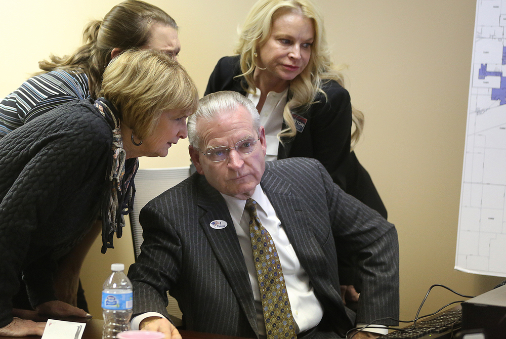 Springfield Mayor Mike Houston gathers his thoughts while joined by wife Carolyn Houston, left, and daughter Michelle Houston at back right moments before making his concession speech to supporters at his Springfield campaign offices on Tuesday evening, Feb. 24, 2015. David Spencer/The State Journal-Register