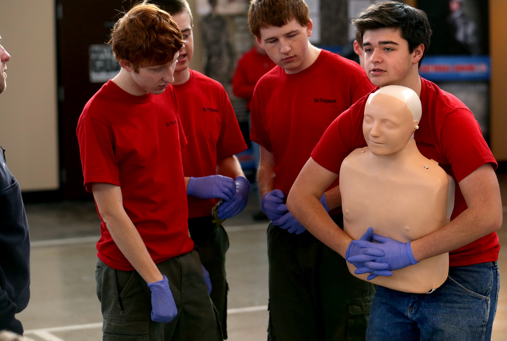 Boy Scout Troop #305 of Pleasant Plains member Hunter Mitchell holds a training mannequin while performing first aid during an airway obstruction emergency scenario while his fellow troop members look on Saturday morning. David Spencer/The State Journal Register