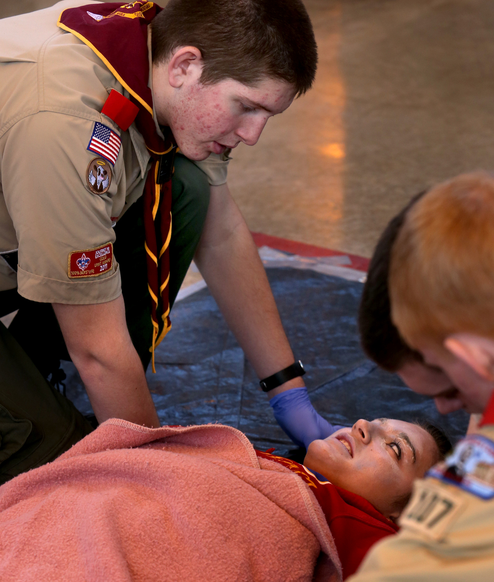 Jacksonville Troop #107 patrol leader Jayden Ware keeps talking with and calming accident victim Marissa Farris after she had a blanket placed on her by Ware's troop mates. David Spencer/The State Journal Register