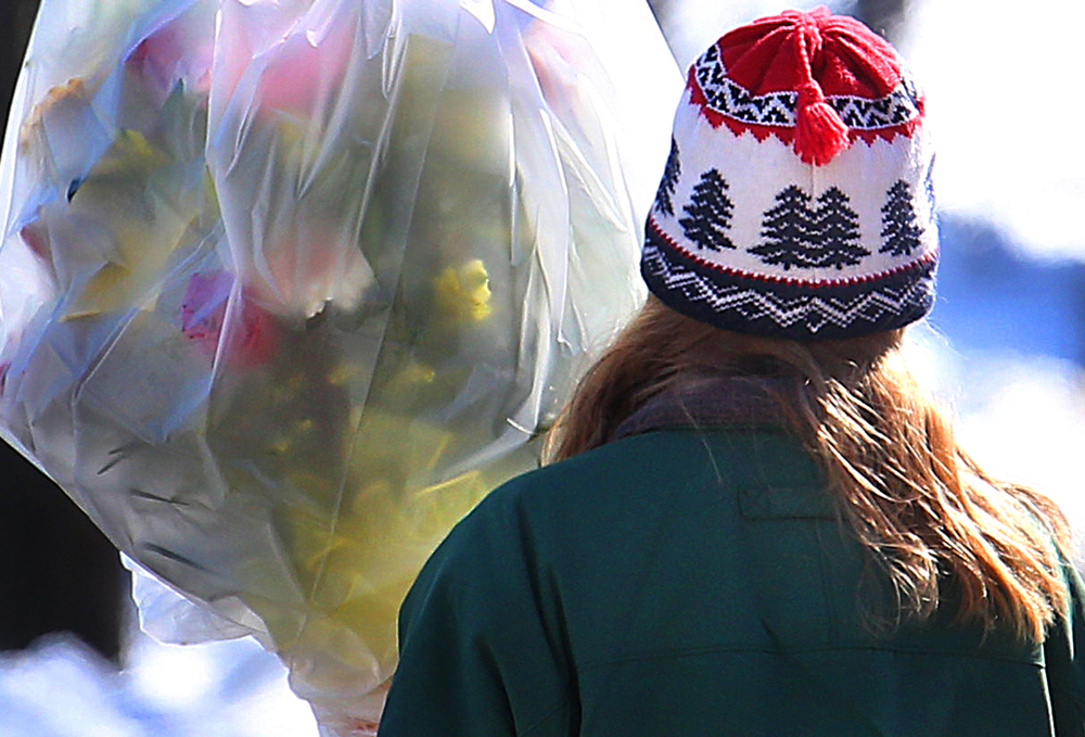 A woman delivering flowers to the Federal building in downtown Springfield had the gift wrapped in heavy plastic to protect against the cold on Friday afternoon, Feb. 27, 2015. This February is shaping up to be one of Springfield's 10 coldest on record.  David Spencer/The State Journal Register