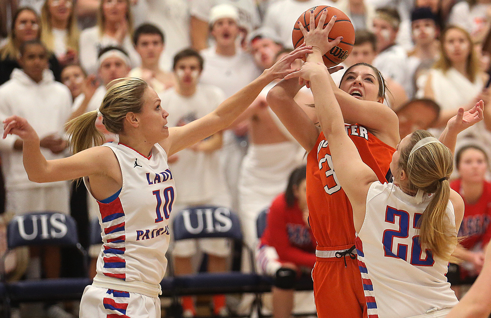 Rochester's Laryn Sapetti puts up a shot in the first half while being defended by Massac player Jessie Douglas at left and Gracyn McBride. Rochester High School defeated Metropolis Massac County 39-35 