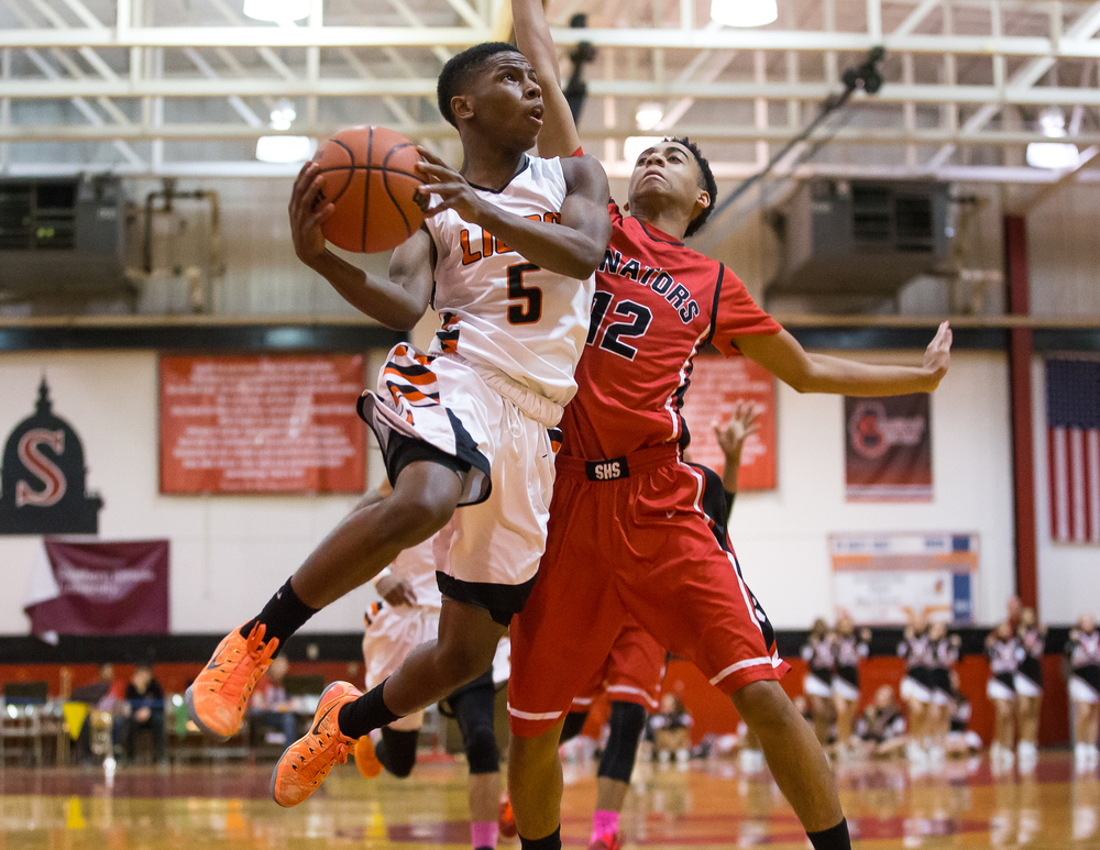 Lanphier's Xavier Bishop (5) drives up to the basket against Springfield's Keon Day (12) in the first half during the Class 3A Springfield Regional at Willard Duey Gymnasium, Tuesday, March 3, 2015, in Springfield, Ill. Justin L. Fowler/The State Journal-Register