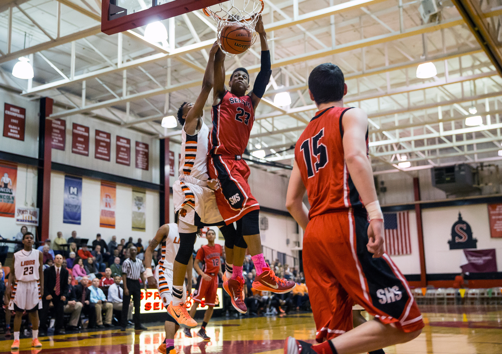 Springfield's Obediah Church (23) dunks the ball as he draws the foul from Lanphier's Cardell McGee (2) in the second half during the Class 3A Springfield Regional at Willard Duey Gymnasium, Tuesday, March 3, 2015, in Springfield, Ill. Justin L. Fowler/The State Journal-Register