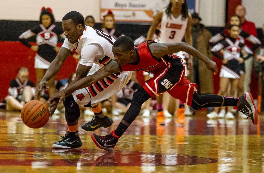Lanphier's Jordan Tribbet (12) steals the ball away from Springfield's Taivon Kincaid (1) in the first half during the Class 3A Springfield Regional at Willard Duey Gymnasium, Tuesday, March 3, 2015, in Springfield, Ill. Justin L. Fowler/The State Journal-Register