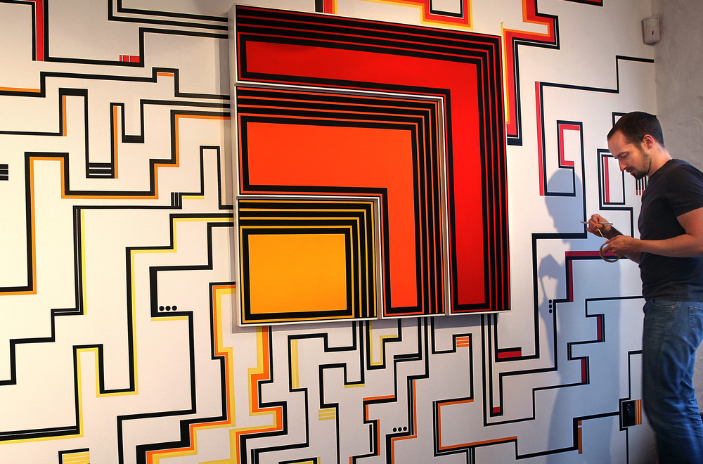 """Pharmacy artist Adam Perschbacher has been creating a site-specific artwork for the opening. Using one entire wall, (8 x 10') he has created an interlocking grid of lines using various widths of colored masking tape emanating from a larger piece at center-an acrylic on masonite panel titled """"The Complacent Proud."""" A devotee of artist Frank Stella, Perschbacher labels his own work Geometric Abstraction, and works on the piece Tuesday evening, March 3, 2015. David Spencer/The State Journal Register"""