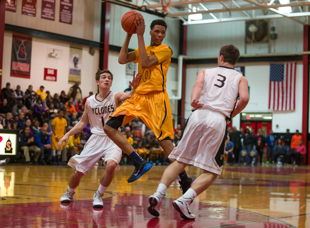 Southeast's Isaiah Walton (10) dishes out a pass to  Harrison Devoe (31) for a three at the buzzer against Southeast to end the first half during the Class 3A Springfield Regional at Willard Duey Gymnasium, Wednesday, March 4, 2015, in Springfield, Ill. Justin L. Fowler/The State Journal-Register
