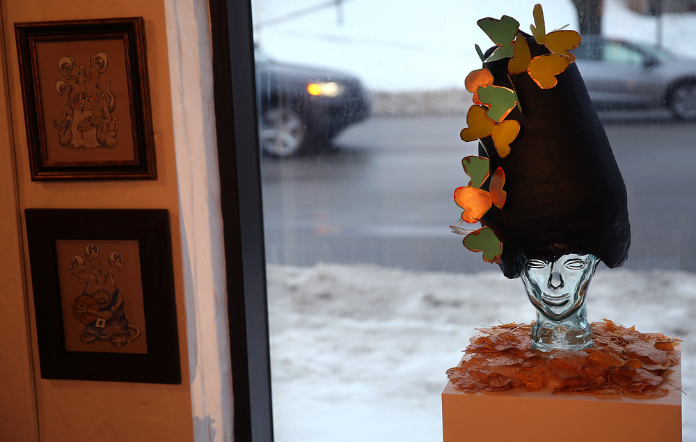 Butterflies take up residence on top of a sculpture featuring a glass head and leaves in this work by Pharmacy artist Laurel Hogan. Framed work by Pharmacy artist Adam Perschbacher are at left. David Spencer/The State Journal Register