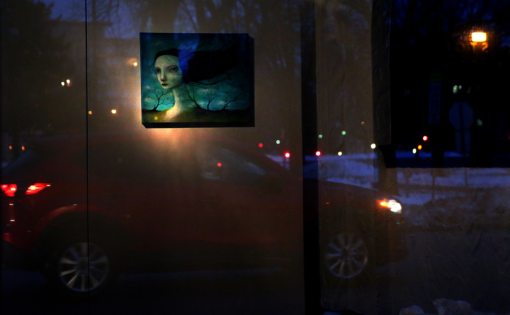 A painting by Pharmacy artist Felicia Olin hung for the show is reflected from the inside of the main exhibition space onto one of the large plate glass windows of the former automobile showroom facing S. Fifth St. David Spencer/The State Journal Register