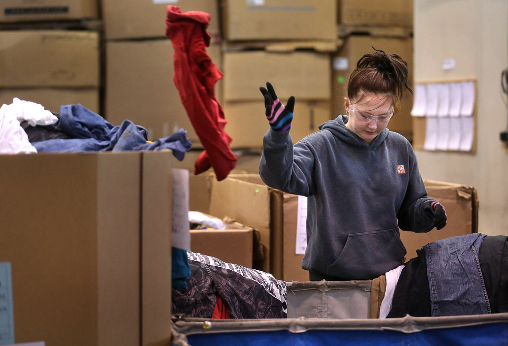Goodwill warehouse employee Arielle Lindsey sorts clothing at the facility on Thursday, March 5, 2015. Lindsey said it takes about five seconds to determine if an article will be sent to a recycling bin or set aside for sale in one of the stores. David Spencer/The State Journal Register
