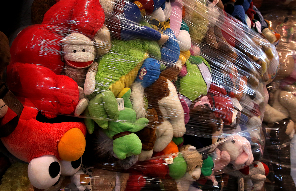 A sock monkey joins thousands of other stuffed toy animals making up one of many shrink-wrapped bales destined for recycling and sale to a third party vendor. David Spencer/The State Journal Register
