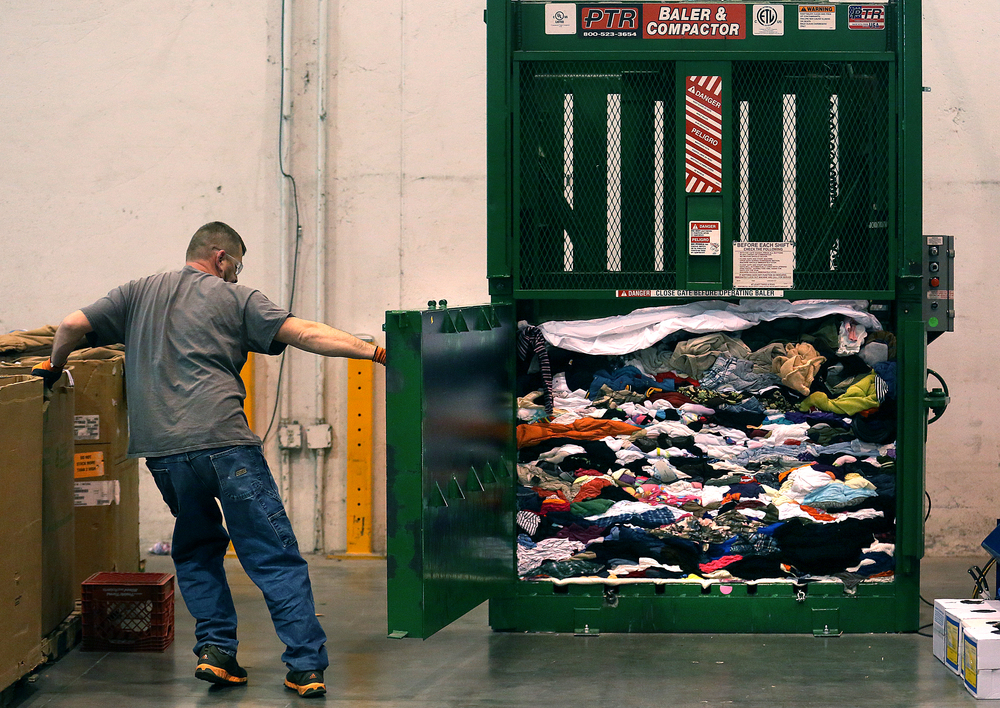 Goodwill warehouse employee Ron Schofield opens the gate to one of the baling and compacting machines at the facility to expose freshly compressed clothing that will be recycled and sold to a third party vendor. David Spencer/The State Journal Register