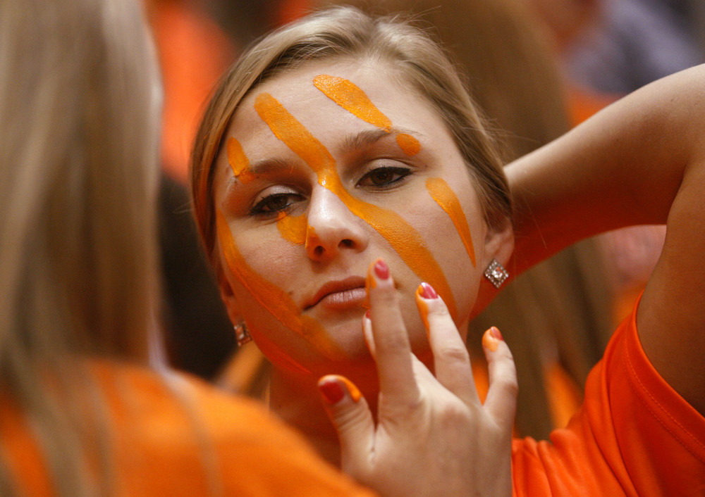 Rochester student Amanda Yeck stands still as a Savannah Williams applies orange face paint before the Rockets face Chicago Bogan during the Class 3A state tournament semifinal at Redbird Arena in Normal Friday, March 6, 2015. Ted Schurter/The State Journal-Register