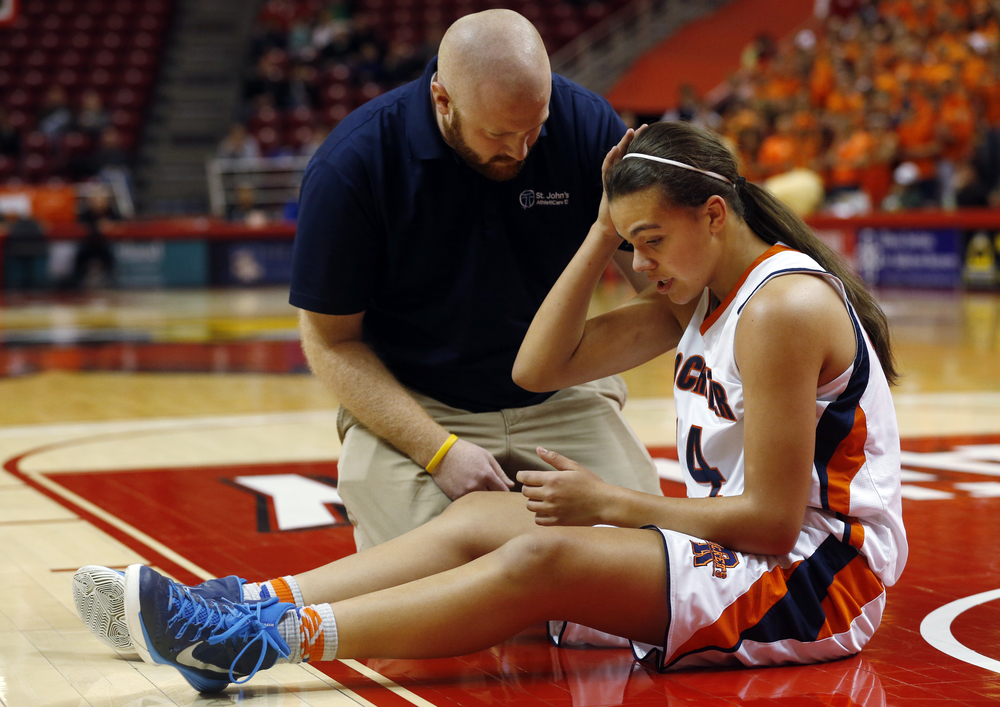 Rochester's Lyric Boone holds her head after getting knocked to the ground by a Chicago Bogan drive during the Class 3A state tournament semifinal at Redbird Arena in Normal Friday, March 6, 2015. Ted Schurter/The State Journal-Register