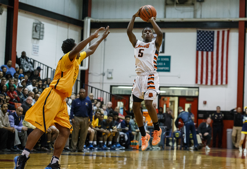 Lanphier's Xavier Bishop (5) nails a step back three in front of Southeast's Mark Johnson (33) in the second half during the Class 3A Springfield Regional title game at the Willard Duey Gymnasium, Friday, March 6, 2015, in Springfield, Ill. Justin L. Fowler/The State Journal-Register
