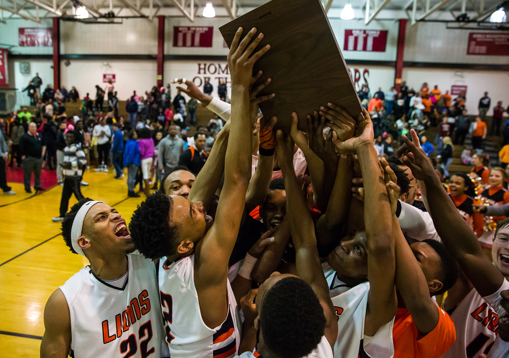 The Lanphier Lions celebrate with their regional title after defeating Southeast 81-80 in the Class 3A Springfield Regional title game at the Willard Duey Gymnasium, Friday, March 6, 2015, in Springfield, Ill. Justin L. Fowler/The State Journal-Register