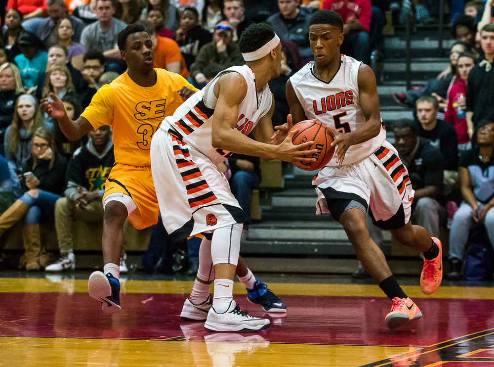 Lanphier's Xavier Bishop (5) grabs the handoff from Daryl Jackson (22) as he avoids the pressure from Southeast's D'Angelo Hughes (30) in the first half during the Class 3A Springfield Regional title game at the Willard Duey Gymnasium, Friday, March 6, 2015, in Springfield, Ill. Justin L. Fowler/The State Journal-Register