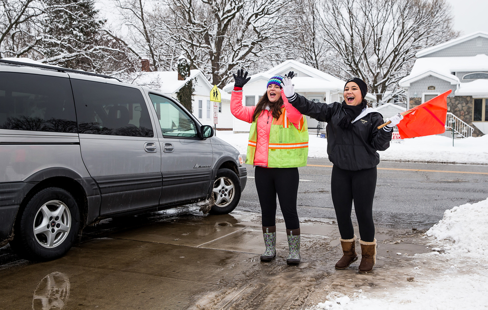 Sacred Heart-Griffin seniors Lydia Lex, center, and Aubrey Henson, right, wave goodbye to those leaving the 56th annual Mostaccioli Dinner as they volunteer to help direct traffic at Sacred Heart-Griffin's West Campus, Sunday, March 1, 2015, in Springfield, Ill. Justin L. Fowler/The State Journal-Register