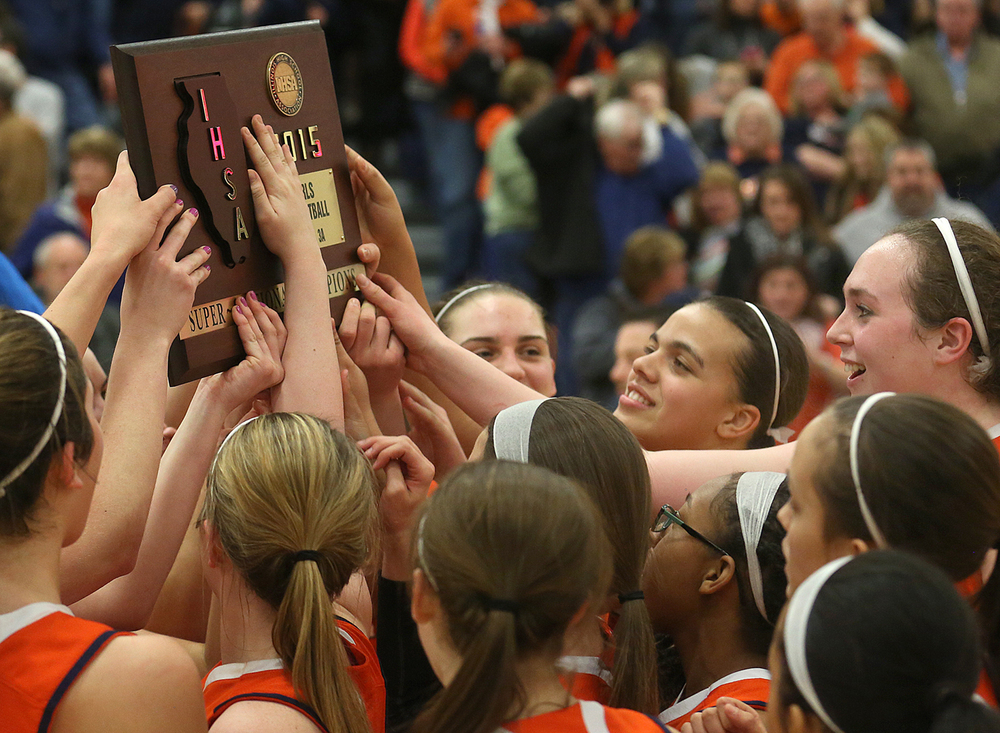 Rochester players celebrate while holding up the championship 3A Super Sectional trophy Monday night. Rochester High School defeated Metropolis Massac County 39-35 