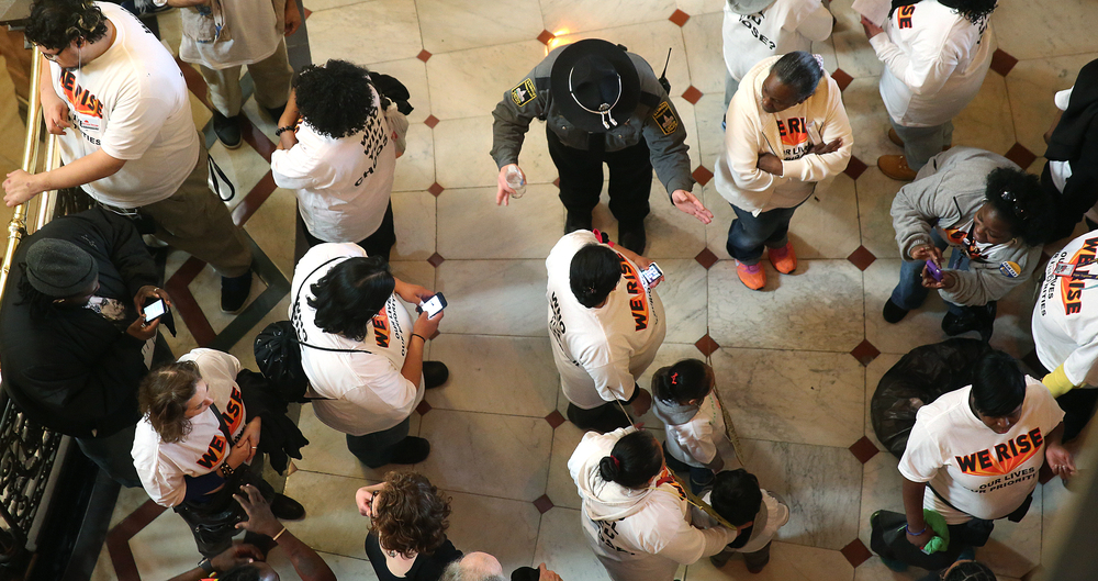 "A Secretary of State police officiers clears a path through protestors inside the State Capitol building in Springfield on Wed. March 11, 2015. As part of ""We Rise"", a national day of action targeting state budget cuts, several thousand people from faith, community and labor organizations including adults, children and clergy affected by Gov. Bruce Rauner's proposed cuts gathered in Springfield to protest. The event began with a rally inside the Capitol building followed by a march to the governor's mansion where a mock ""funeral"" for the ""99%"" took place. David Spencer/The State Journal-Register"