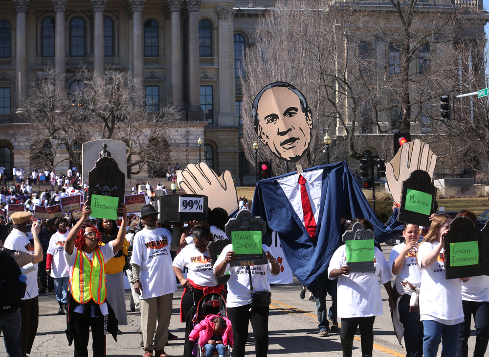 "Protestors walk with a large caricature of Gov. Bruce Rauner and a mock coffin east on Capitol Ave. towards the Governor's Mansion on Wed. March 11, 2015. As part of ""We Rise"", a national day of action targeting state budget cuts, several thousand people from faith, community and labor organizations including adults, children and clergy affected by Gov. Bruce Rauner's proposed cuts gathered in Springfield to protest. The event began with a rally inside the Capitol building followed by a march to the governor's mansion where a mock ""funeral"" for the ""99%"" took place. David Spencer/The State Journal-Register"