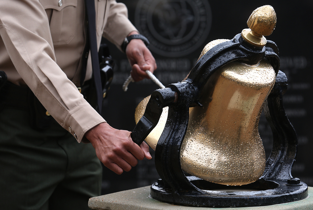 Illinois State Trooper Timothy Black rings the bell during the Bell Ceremony outside the Academy Friday morning.  David Spencer/The State Journal-Register